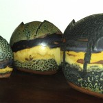 Three clay pots painted to create a landscape scene.